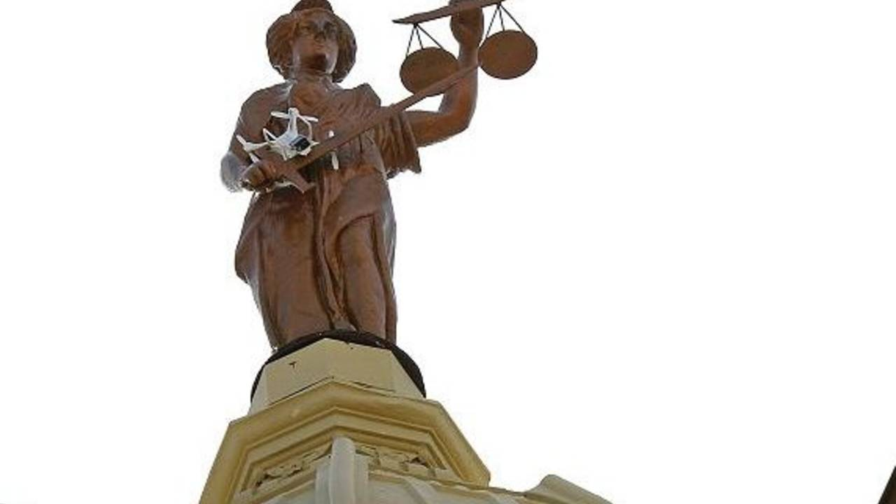 Drone helicopter stuck atop a 100 foot statue of Lady Justice