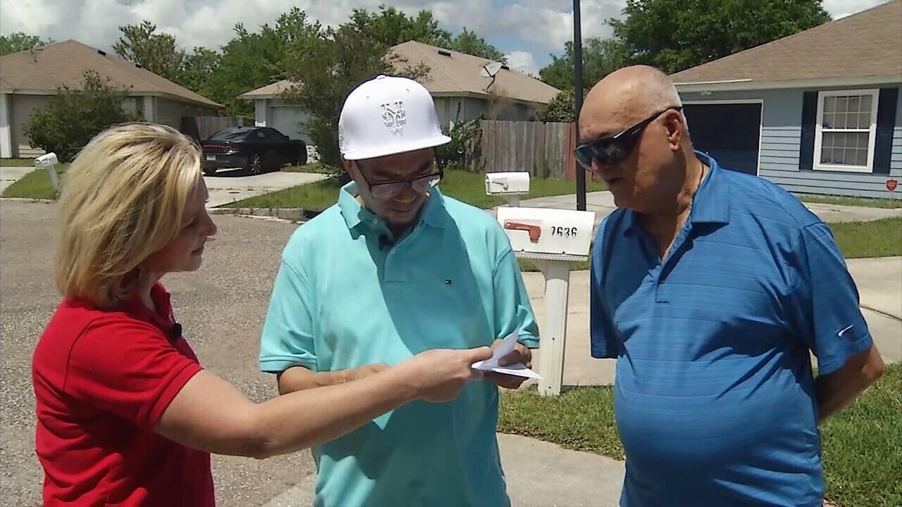 Castillos and Jen Waugh looking at copy of check