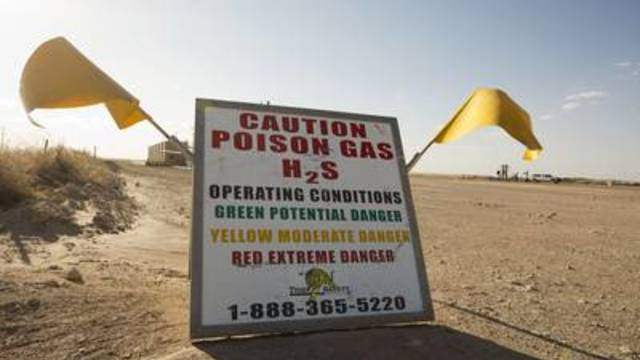 A sign near a natural gas flare less than a mile away from Sue Franklin's home warns of the presence of hydrogen sulfide.