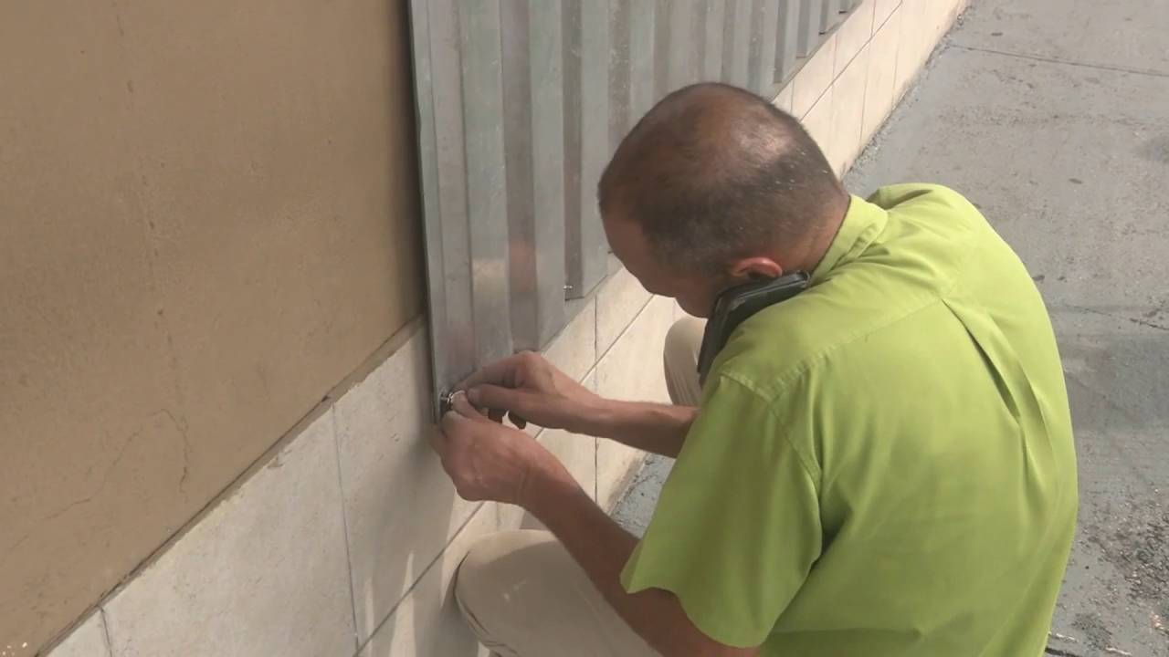 man putting shutters on business windows in Puerto Rico