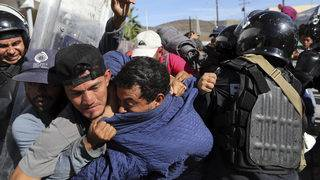 Migrants enveloped in tear gas after heading toward US