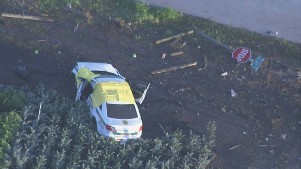 wrecked Miami-Dade police cruiser next to stop sign on ground