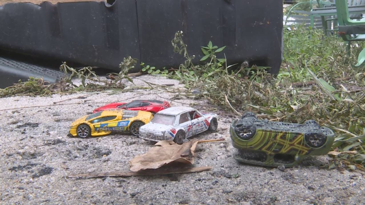 Toy cars on ground outside burned mobile home at Holiday Ranch Mobile Home Park