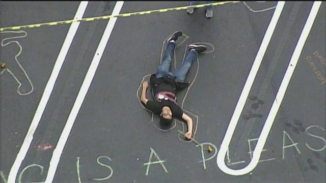 student in chalk outline at Publix 'die-in' protest