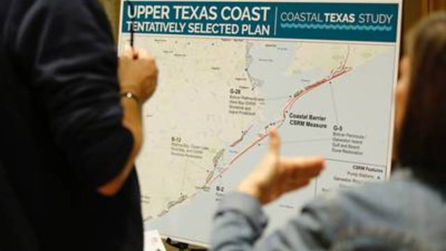 People discuss a map of a coastal barrier system at an Army Corp of Engineers meeting about the Texas Coastal Study on Wednesday in Galveston.