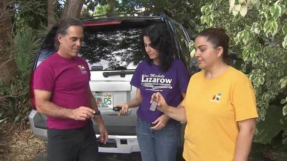 Hallandale Beach commissioners and Annabelle Taub hold tracking devices