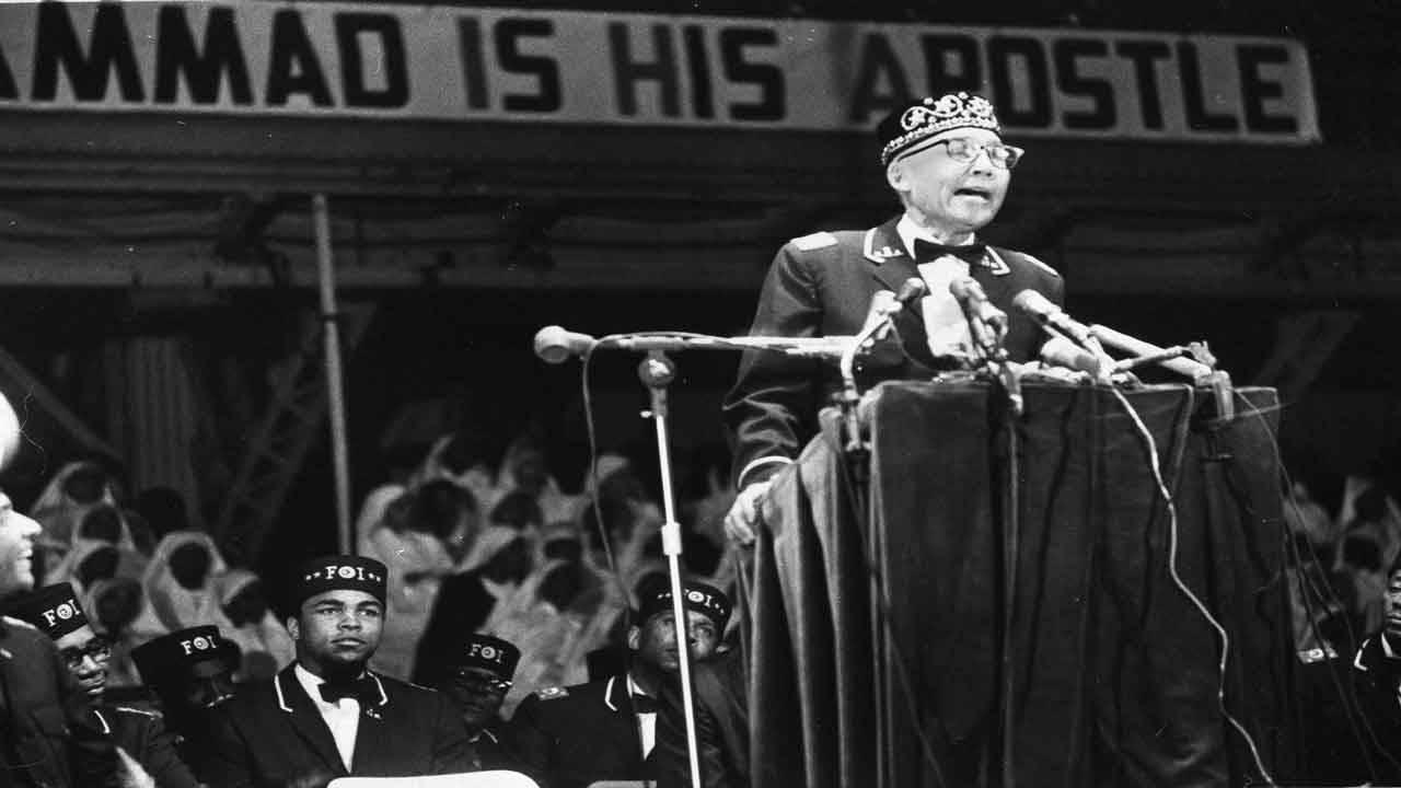 Elijah Muhammad speaks to black Muslims in 1967 as Muhammad Ali listens