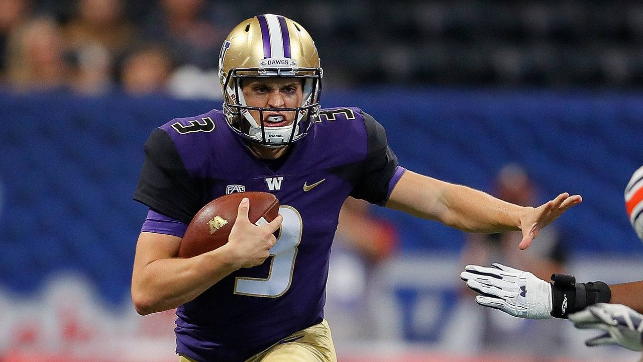 78a68632b Jake Browning  3 of the Washington Huskies rushes away from Darrell  Williams  49 and Andrew Williams  79 of the Auburn Tigers at Mercedes-Benz  Stadium on ...