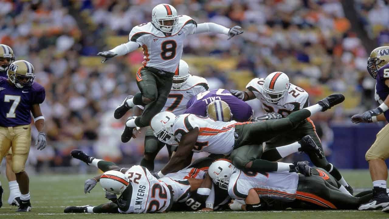 Miami Hurricanes safety Mike Rumph jumps over pile of players vs Washington Huskies in 2000