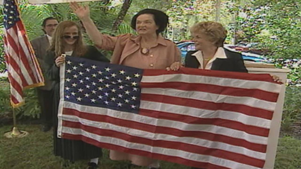Roxcy Bolton holds US flag during 1999 ceremony