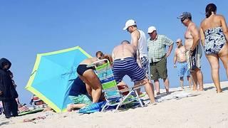 Winds lift beach umbrella, launching it through a tourist's ankle