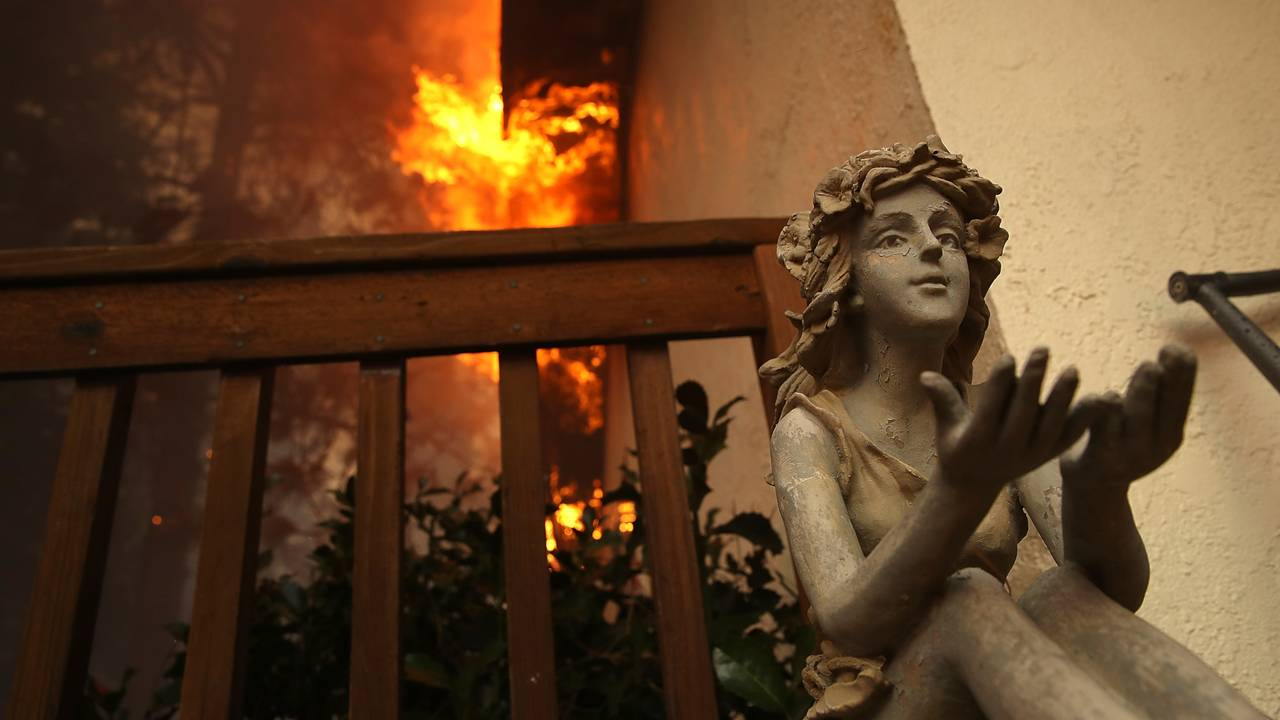 statue on deck of burning home, California's Camp Fire91512860-75042528