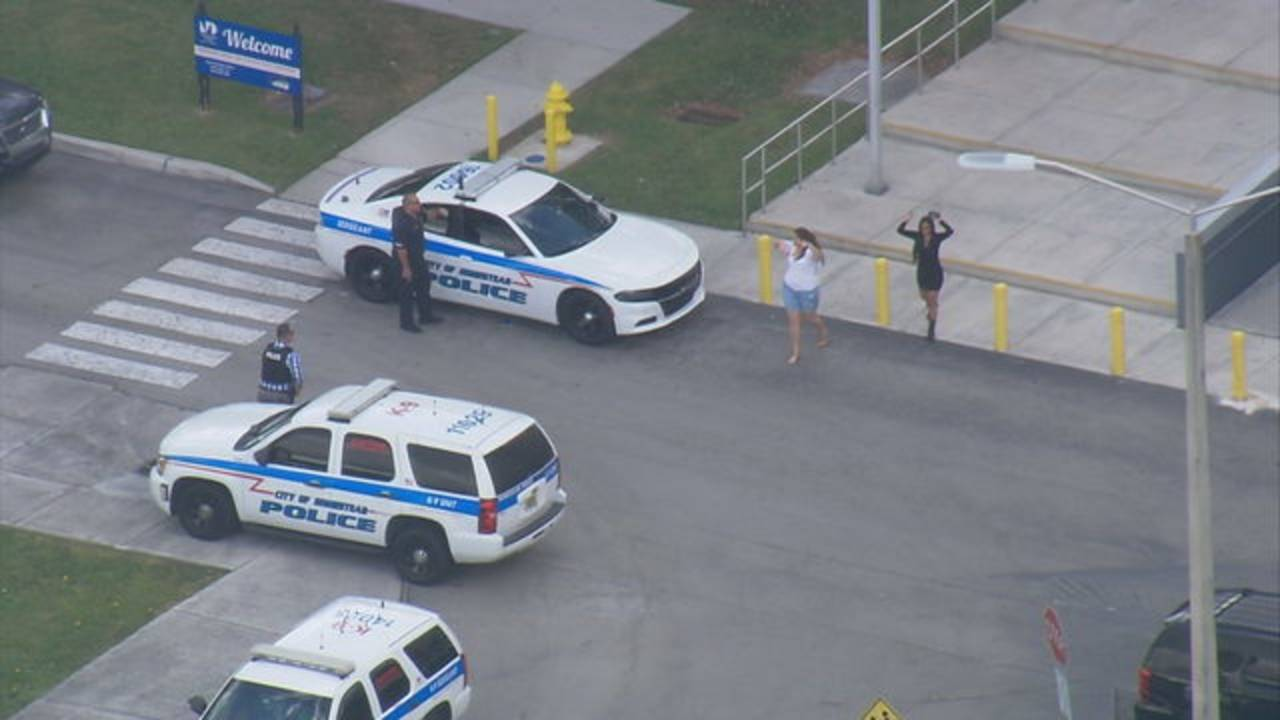 People walking out of Miami Dade College Homestead Campus with their hands up