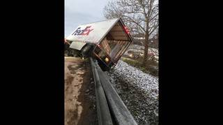 UPDATE: Driver charged after tractor-trailer hangs over an overpass