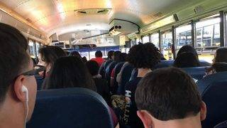 High School students sit on floor, in aisle of Orange County school bus