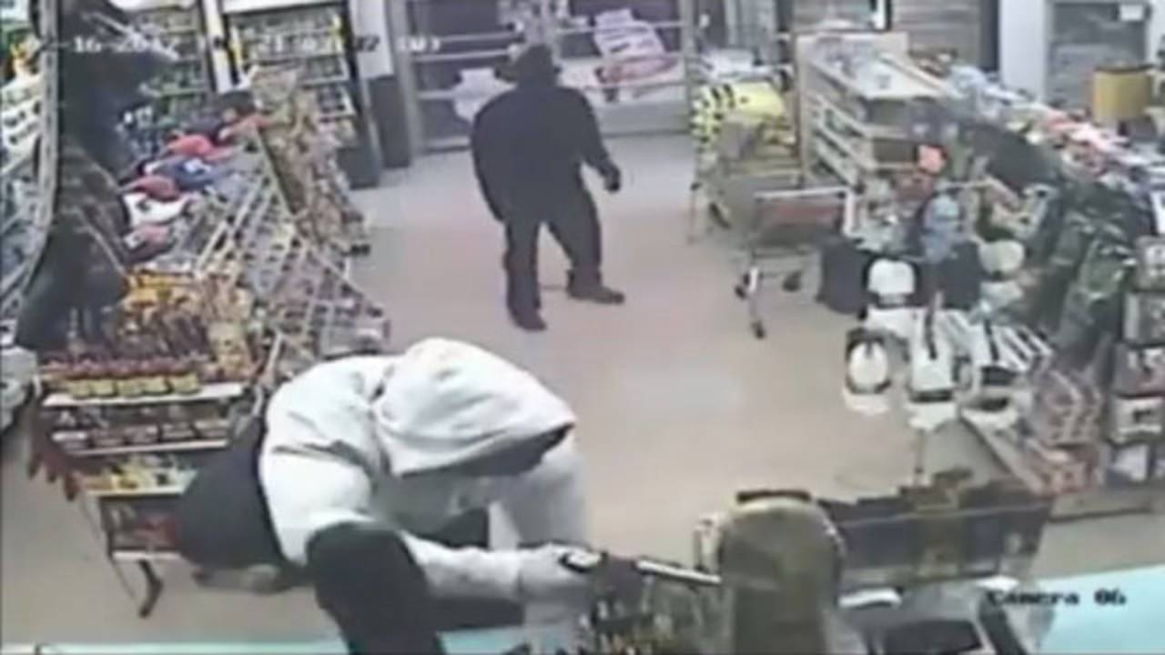 Armed robber with gun on counter