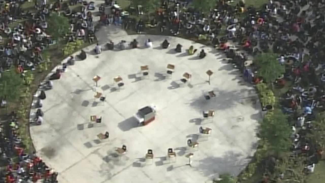 Cooper City High School students surrounding empty desks in honor of Parkland victims