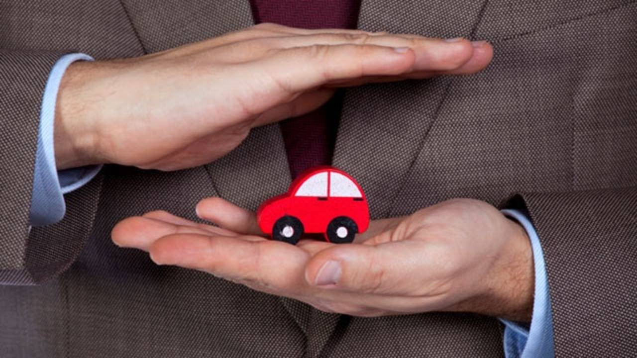 auto insurance agent with tiny car in hands_6710812