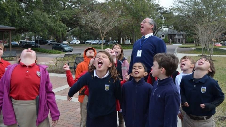 Kids try to catch snowflakes with tongue_30599726