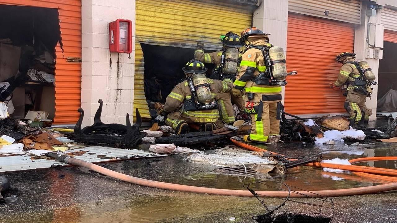 Firefighters outside burned storage unit
