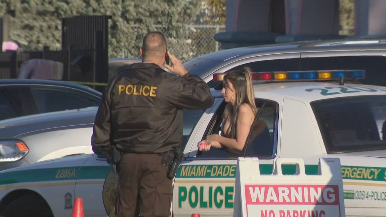 Woman leaning out window of police car after Booby Trap shooting