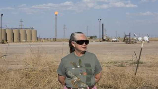 Sue Franklin stands in front of a natural gas flare near her home in Balmorhea.