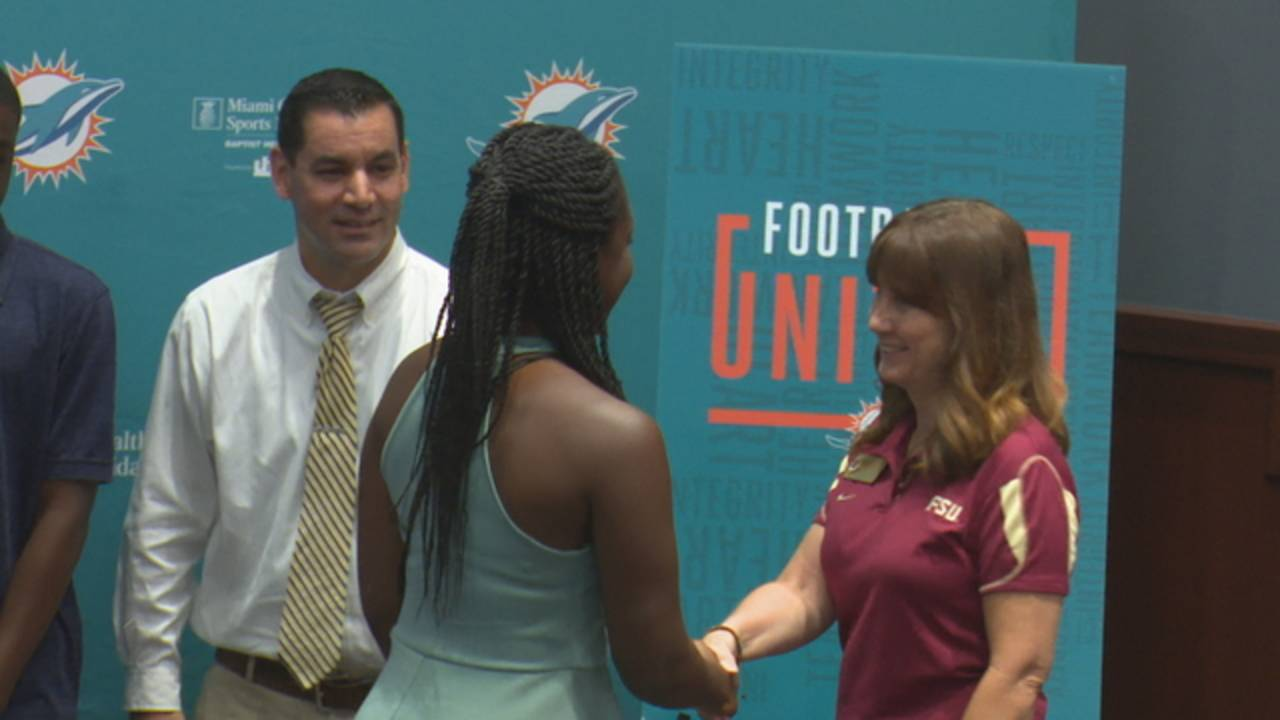 Dolphins scholarship recipient Valicia Browne shakes hands with Florida State University representative