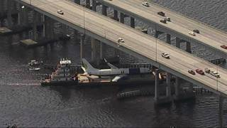 Boeing 737 towed away on barge along St  Johns River