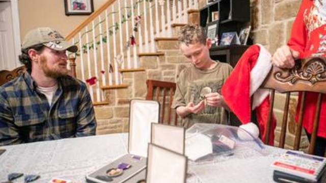Joshua Raines (left) and his son go through the combat veteran's medals in their dining room. Raines, a medical marijuana advocate and user, served in Afghanistan and was wounded in 2010 causing severe PTSD and seizures.