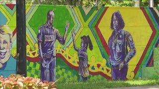 Officers take orders from street artist to paint Liberty City wall with teens