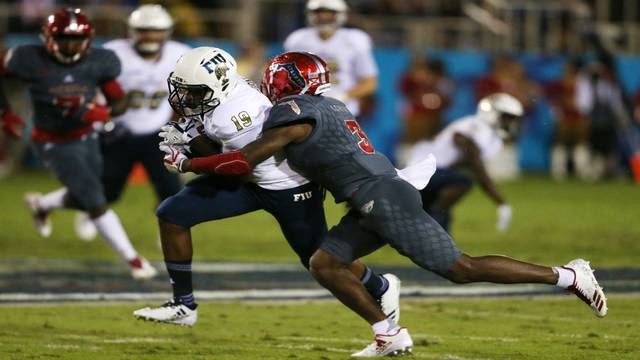 FIU's Shelton Lewis tackled by FAU's Shermar Thornton