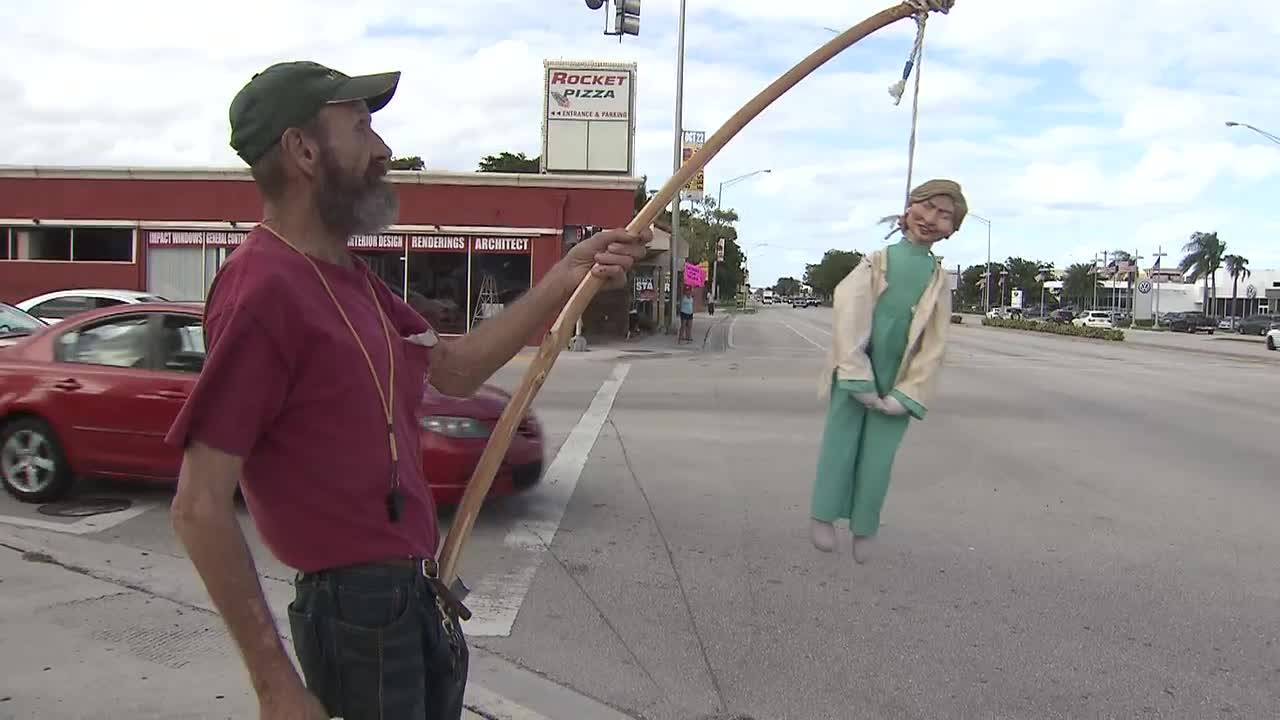 Man holding Hillary Clinton doll by rope