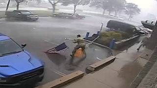 Soldiers rush to pick up American flag during severe storm