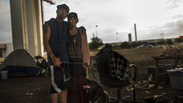 Harold Hicks (left) visits Austin residents experiencing homelessness with his wife, Gypsy. He used to be homeless but has since found a home and steady work.