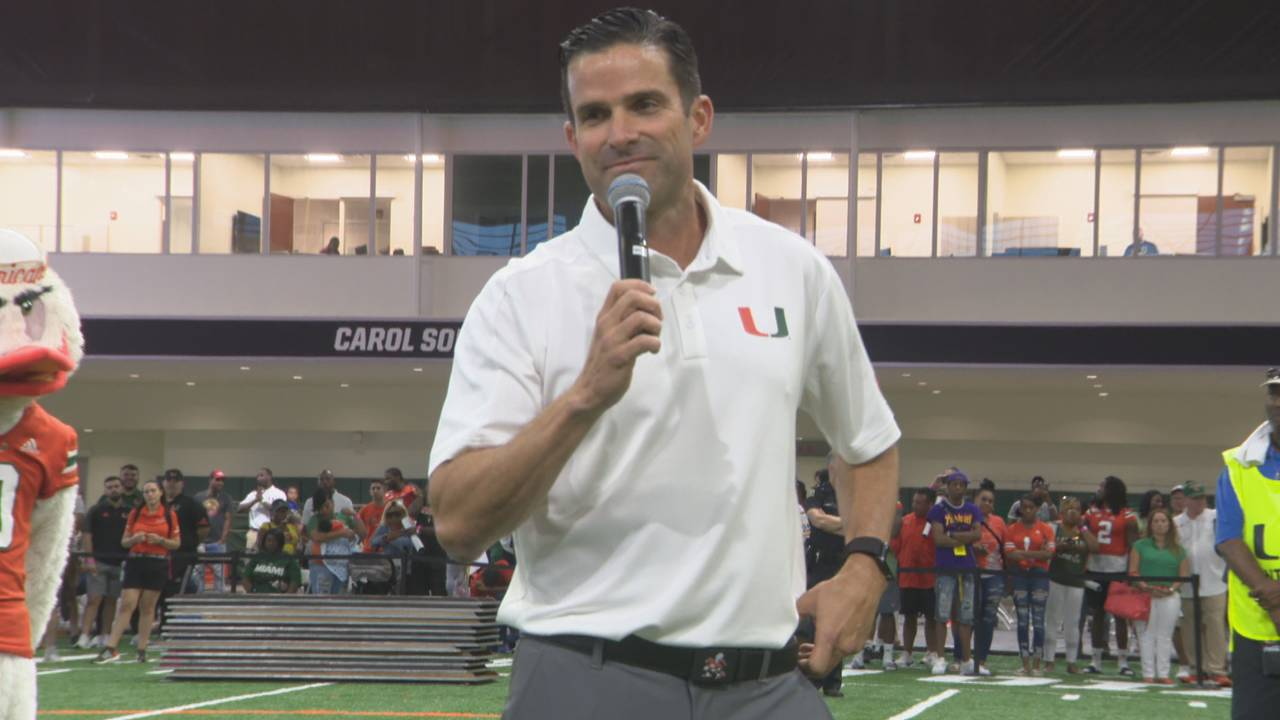 Miami Hurricanes head coach Manny Diaz holding microphone