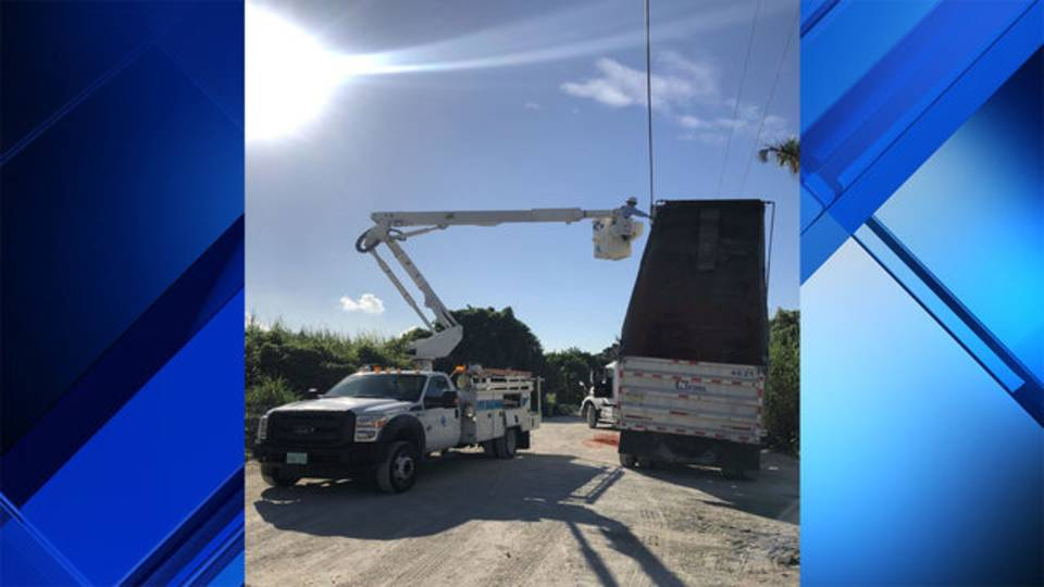 FPL worker near dump truck on power line