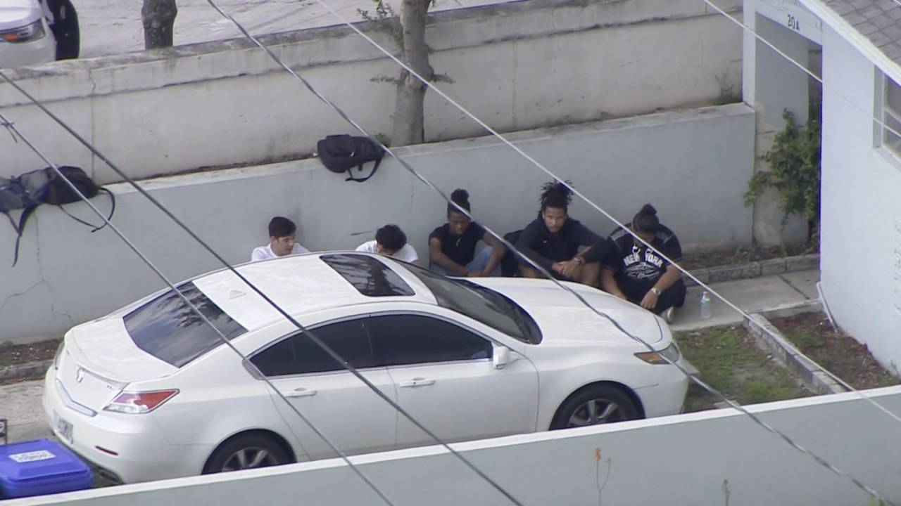 People sitting on ground outside Miami home