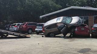 SUV hits multiple vehicles, lands on top of parked car