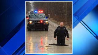 Grand Blanc Township police share picture of officer standing in massive pothole