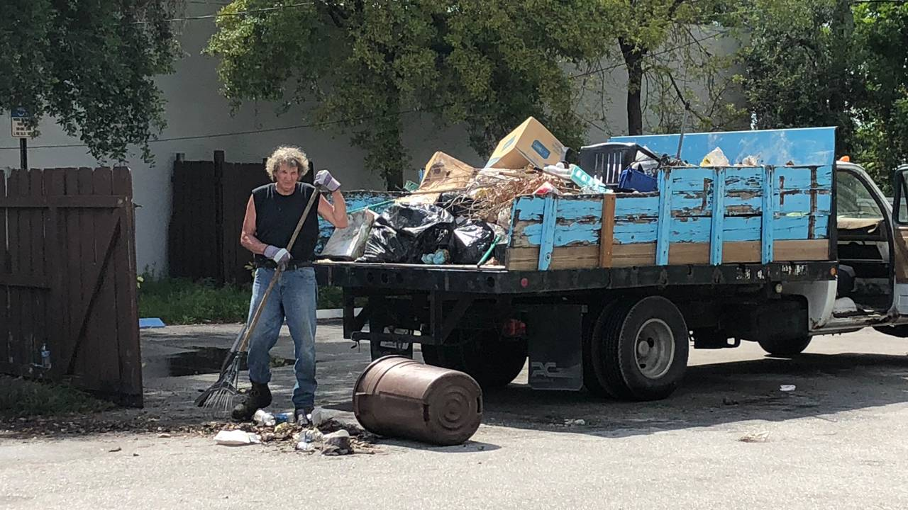 Worker cleaning up trash outside Rin Kin Bing