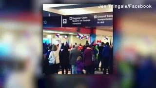 Airport travelers sing National Anthem to pay respects to fallen military heroes