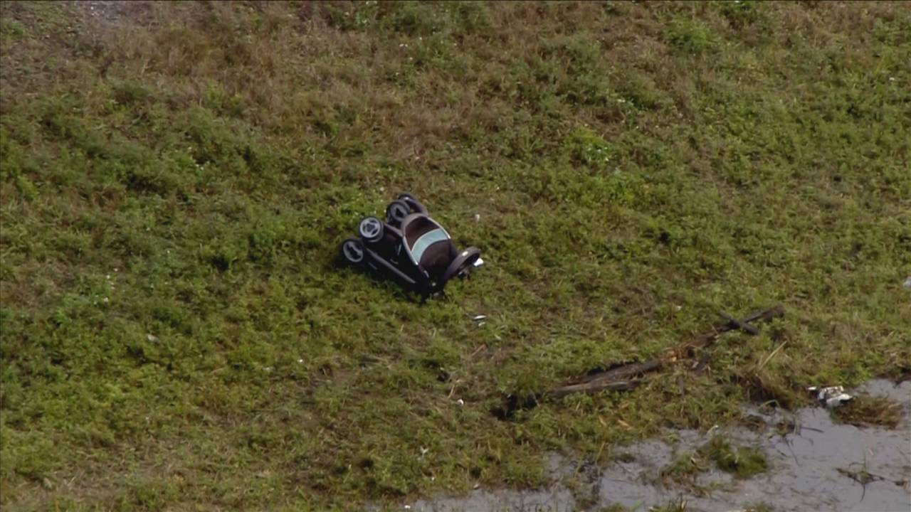 Baby stroller on embankment by vehicle in pond in Lauderhill