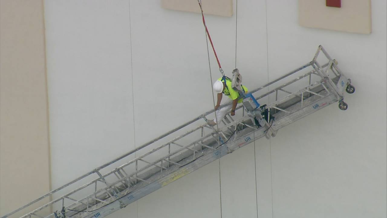 Man dangling from safety harness at construction site after scaffold gives way