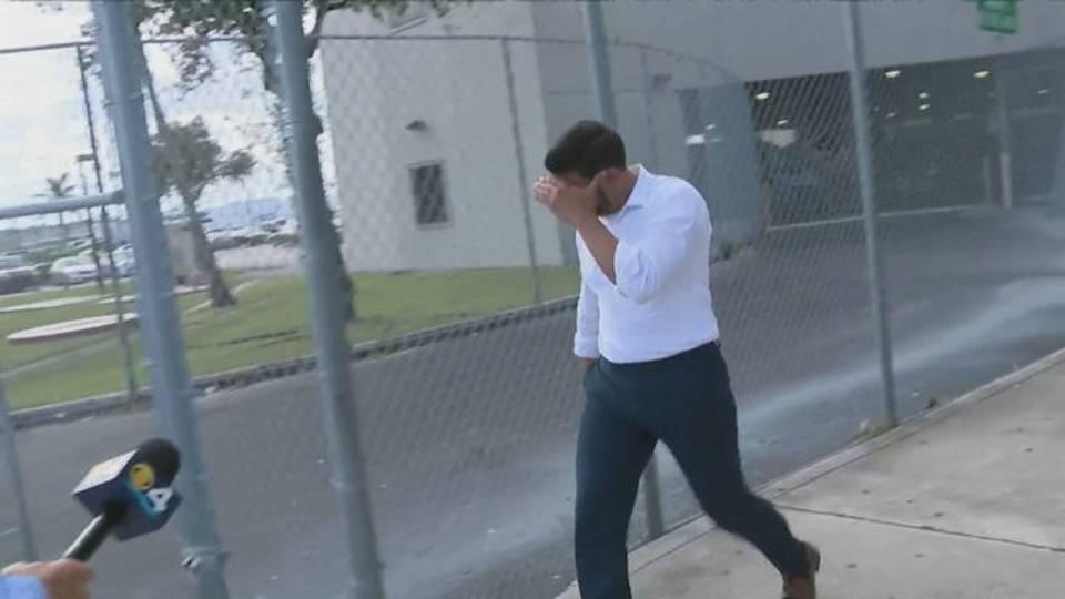Alexander Diaz de Villegas covering face as he leaves jail